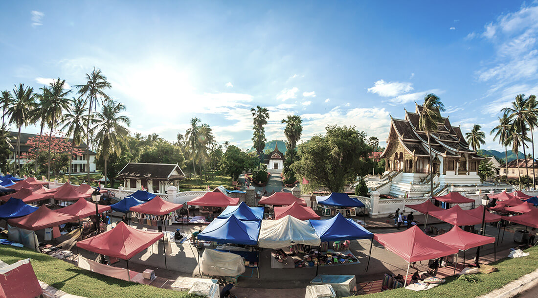 Luang Prabang market stalls with the Royal Palace and Wat Xiengthong temple in the background