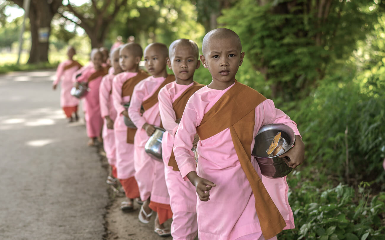 Novice monks line up for alms in village along the Chindwin River, Myanmar