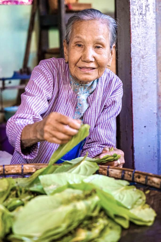 An elderly woman peddling her wares at a local Pakokku market