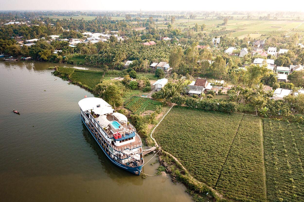 Heritage Line Jayavarman moored alongside a village in the Mekong Delta