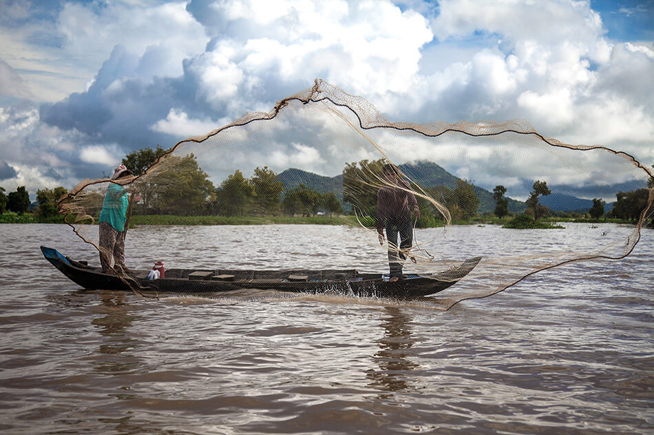 Fishermen cast their net into the Tonle River