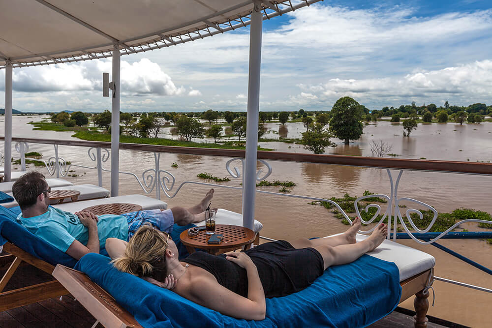 Guests enjoying the passing river scenery from the terrace deck's sun loungers