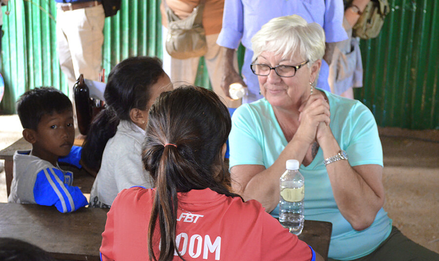 A guest interacts with children in Cambodia's Tonle region