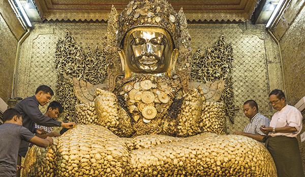 Visitors applying gold leaf to the Mahamuni image