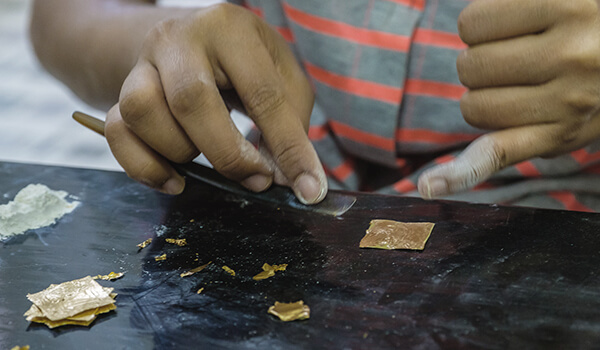 Woman placing a thing sheet of gold on bamboo paper