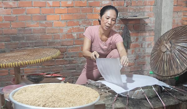 Woman preparing rice paper at a rice and candy workshop in Cai Be, Vietnam