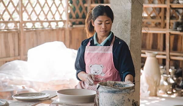 Young villager using pottery wheel in Andong Russei village, Kampong Chhnang (Cambodia)