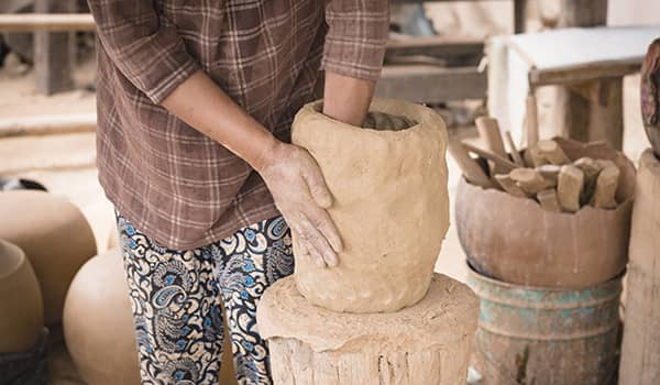 Craftswoman shaping a pottery by hand in Andong Russei village, Kampong Chhnang (Cambodia)