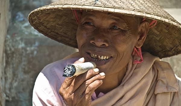 Elderly Burmese woman smoking Cheroot cigar